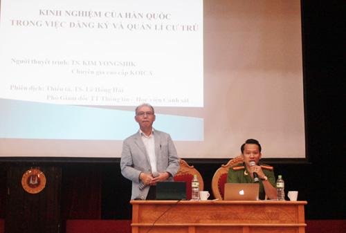Tiến sĩ Kim YongShik (bên trái) và Thiếu tá, TS. Lê Hồng Hải thuyết trình chia sẻ kinh nghiệm của Hàn Quốc về đăng ký và quản lý cư trú