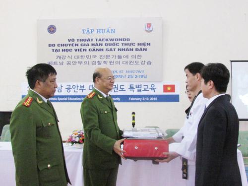 Đại tá Trần Minh Chất, Phó Giám đốc Học viện CSND tiếp nhận các thiết bị phục vụ công tác học tập  do đại diện đoàn chuyên gia Hàn Quốc (NIS) trao tặng