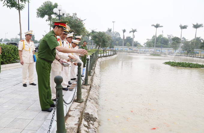 Deputy Minister Nguyen Duy Ngoc and the delegates feed the fishes at the fishpond of the PPA
